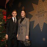 Joshua Kimmich kommt klassisch im Anzug mit schwarzer Krawatte, Freundin Lina trägt einen Mantel mit Hahnentrittmuster überm schwarzen Kleid