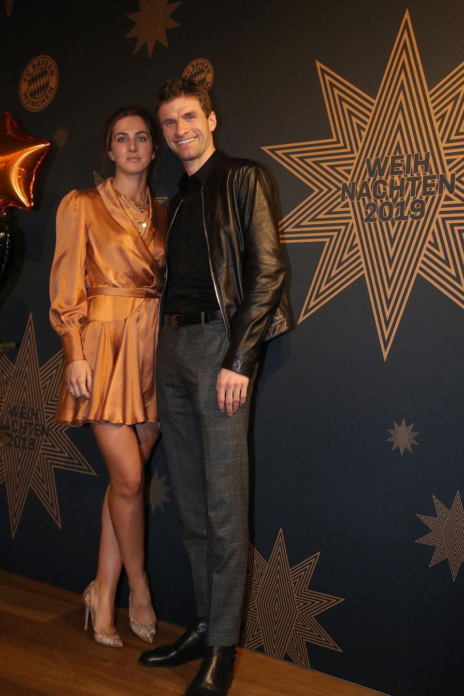 Das Kleid von Lisa Müller ist ähnlich geschnitten wie das von Anna Lewandowska – strahlt aber in sattem Gold. Ehemann Thomas Müller kommt lässig in Lederjacke zur Weihnachtsfeier.