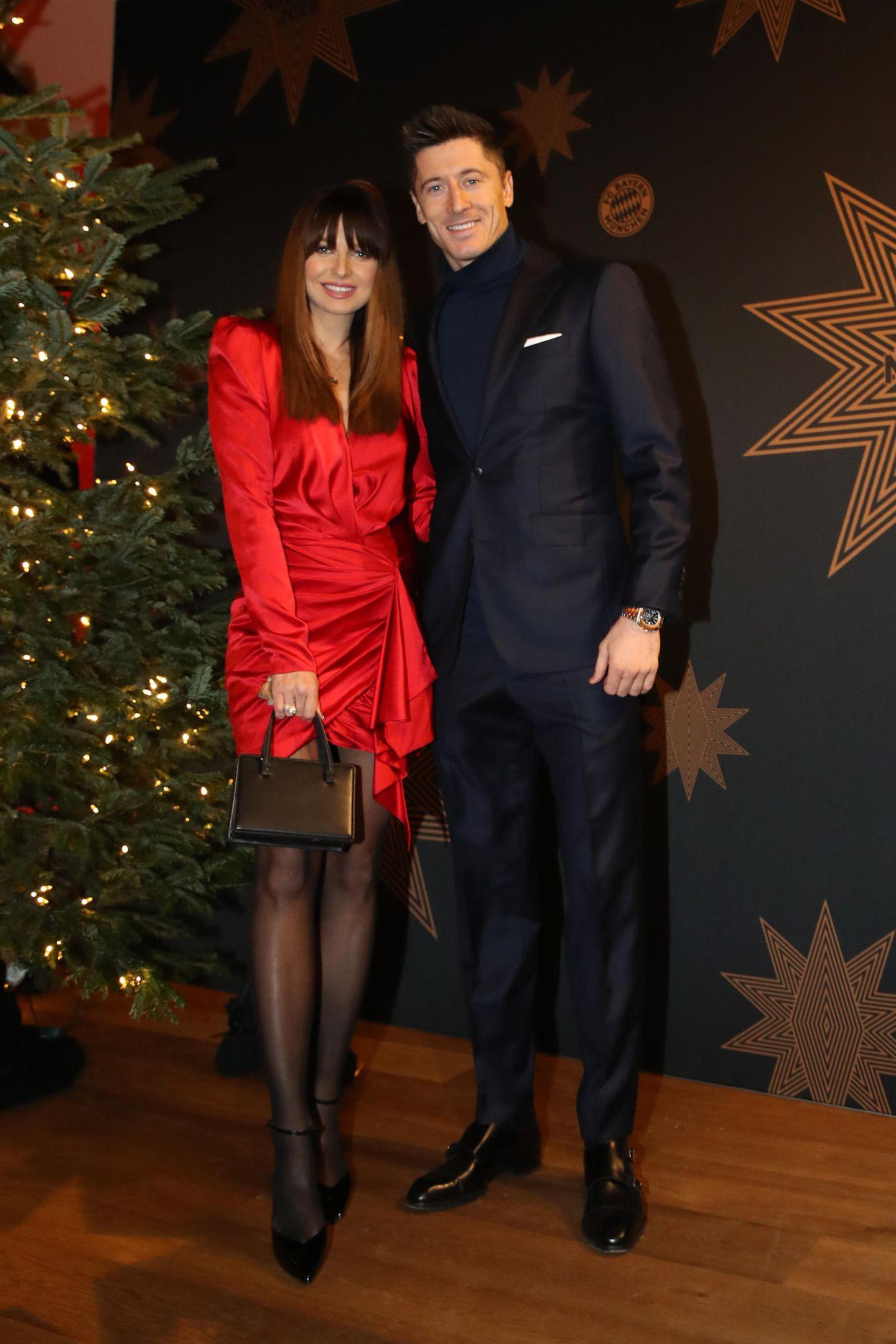 Die schwangere Anna Lewandowska begleitete ihren Gatten Robert Lewandowski zur Weihnachtsfeier des FC Bayern München. Sie trägt ein fließendes rotes Mini-Kleid, das in der Taille gewickelt wird. Robert setzt auf einen schmal geschnittenen Anzug.
