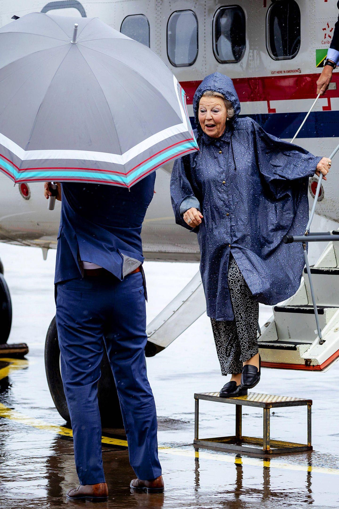 Bei der Ankunft von Prinzessin Beatrix auf der Insel Saba regnet es in Strömen. Zum Glück ist die Prinzessin mit einem Regenmantel gegen das schlechte Wetter bestens gerüstet und auch ein Schirmträger steht schon bereit.