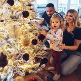Die kleine Mia ist ganz entzückt den Weihnachtsbaum mit ihren Eltern Dominic und Sarah Harrison zu schmücken.