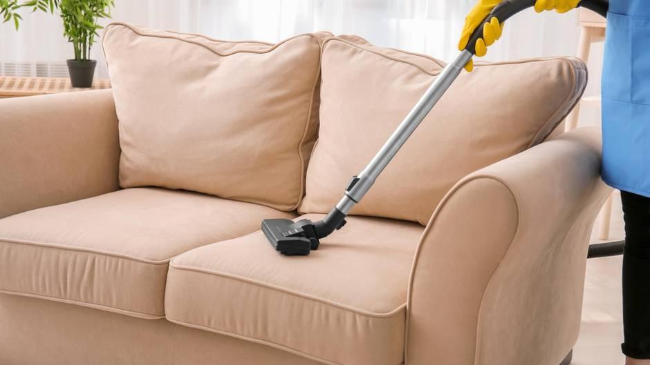 Frau reinigt Sofa