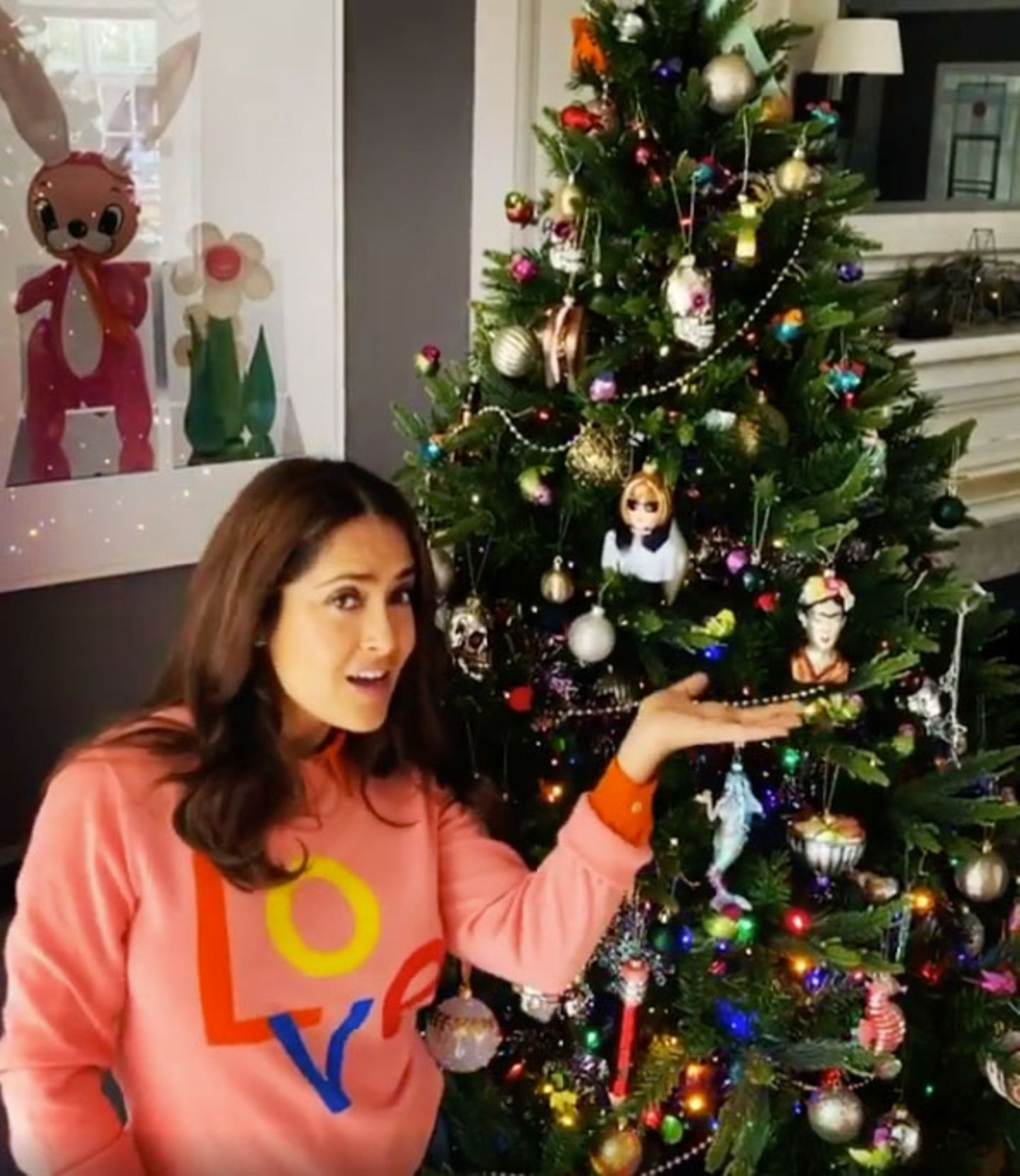 """Im Pullover mit klarer """"Liebes""""-Botschaft präsentiert uns Schauspielerin Salma Hayek ihren bunt dekorierten Weihnachtsbaum. We like!"""