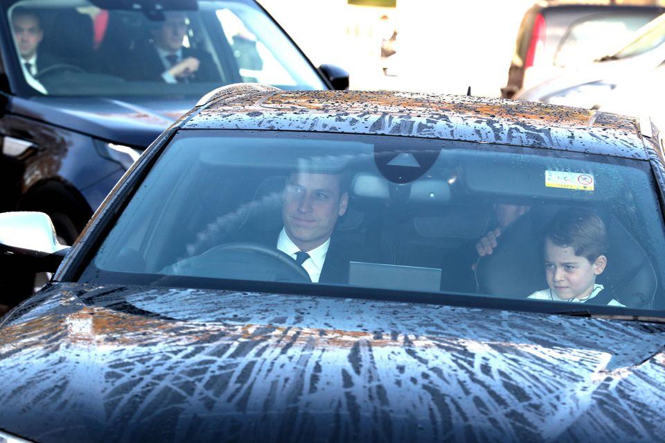 Prinz William und Prinz George auf dem Weg vom Kensington zum Buckingham Palast. Im hinteren Teil des Wagens sitzt ein Bodyguard.