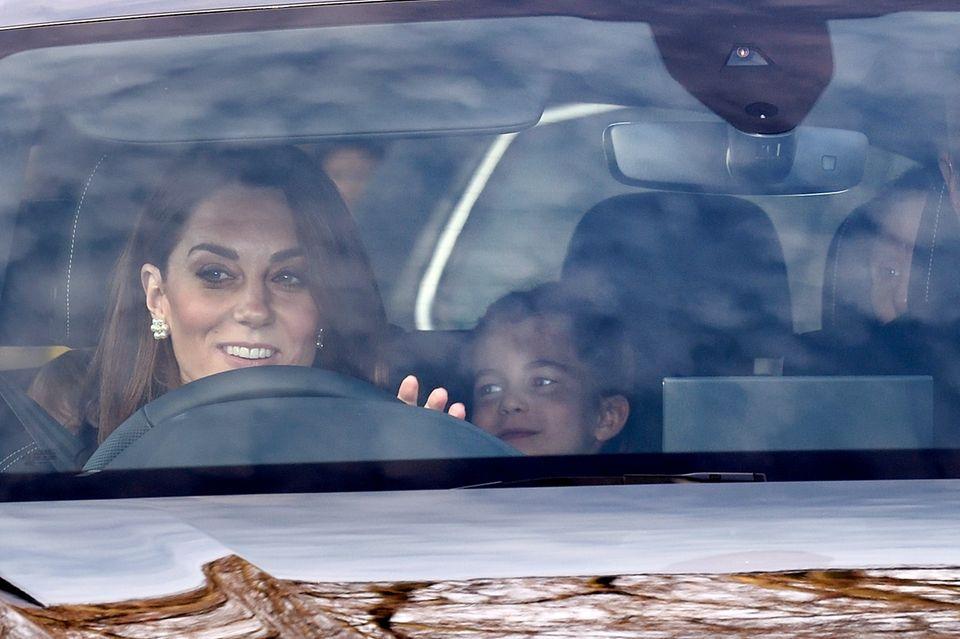 Herzogin Catherine fährt ihre Kinder Prinz Louis (zu erkennen am blonden Haarschopf direkt hinter Kate), Prinzessin Charlotte (hinten Mitte) und NannyMariaTeresa Turrion Borrallo (hinten rechts) zum Palast. Neben Kate hat ein Personenschützer Platz genommen.