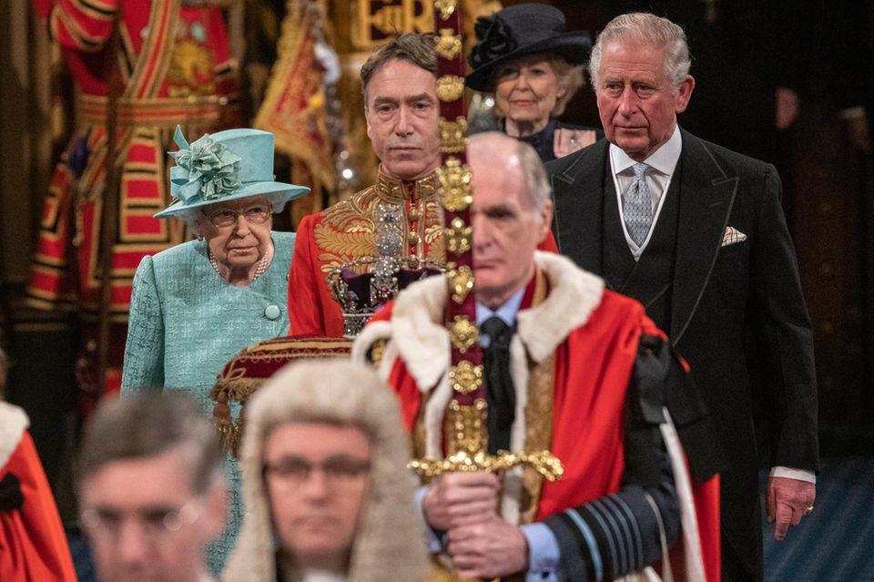 Die Queen wird von Prinz Charles zum Thron im Oberhaus geführt. In ihrer Rede enthüllt die Königin den Abgeordneten das Programm der mehrheitlich konservativen Regierung für das kommende Jahr.