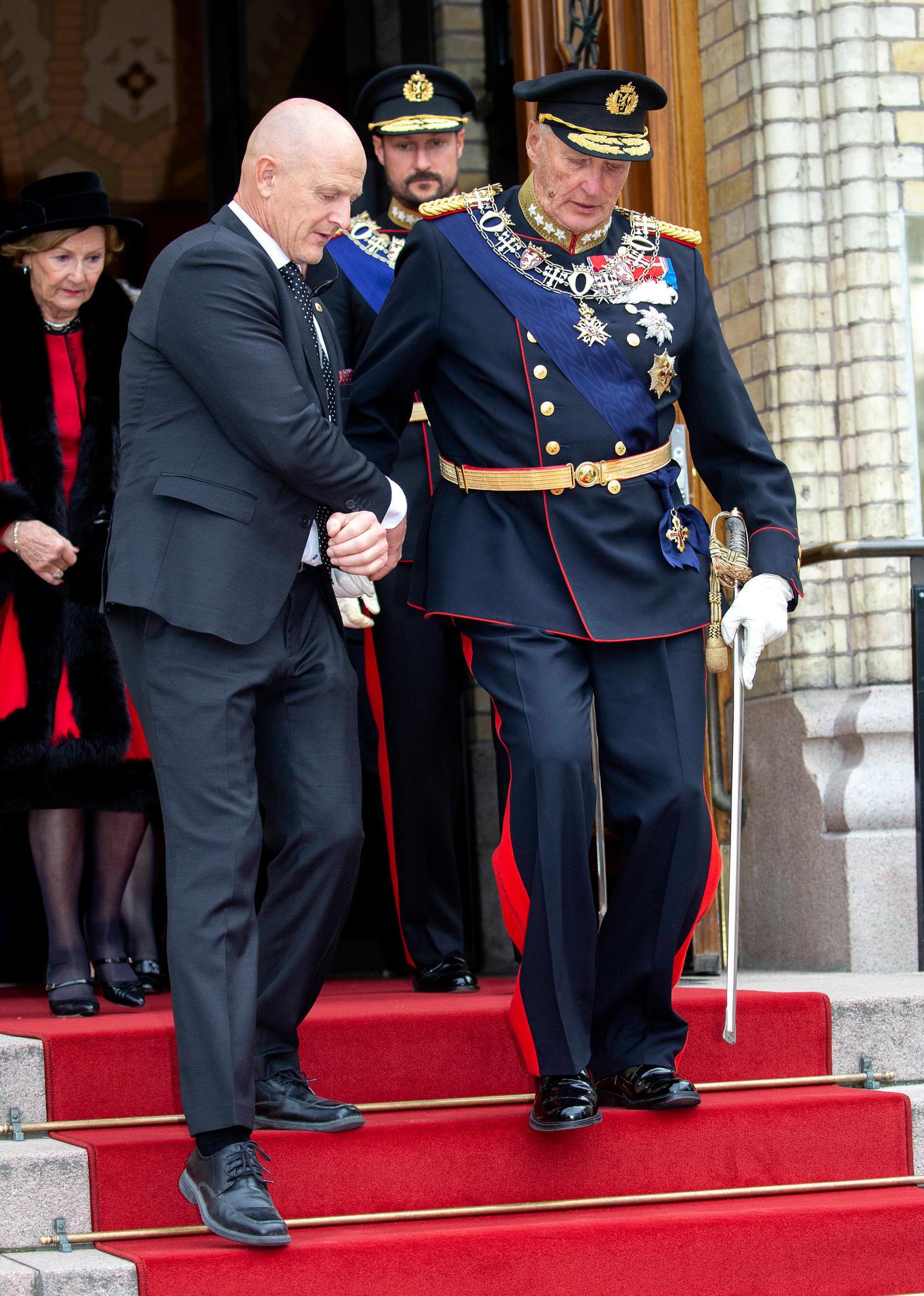 König Harald wird gestützt, hinter ihn gehen Königin Sonja undPrinz Haakon. Das Foto entstand im Oktober 2019.