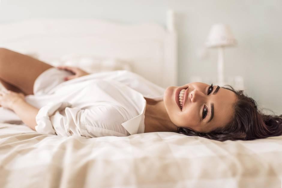 Frau liegt im Bett und hat nur ein weißes Hemd an
