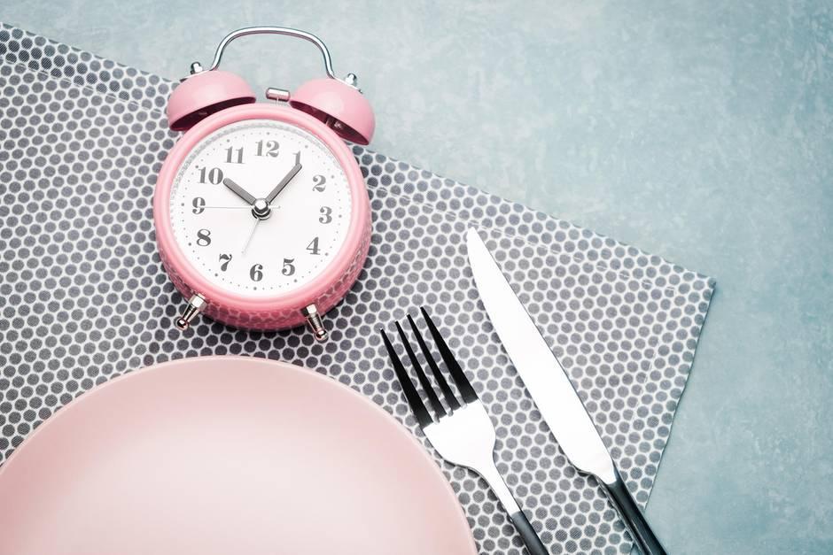 ein leerer,rosa Teller, daneben Besteck und ein rosa Wecker