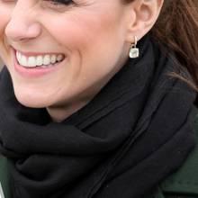 Herzogin Kate lächelt und trägt glitzernde Creolen Ohrringe mit Edelstein-Anhängern