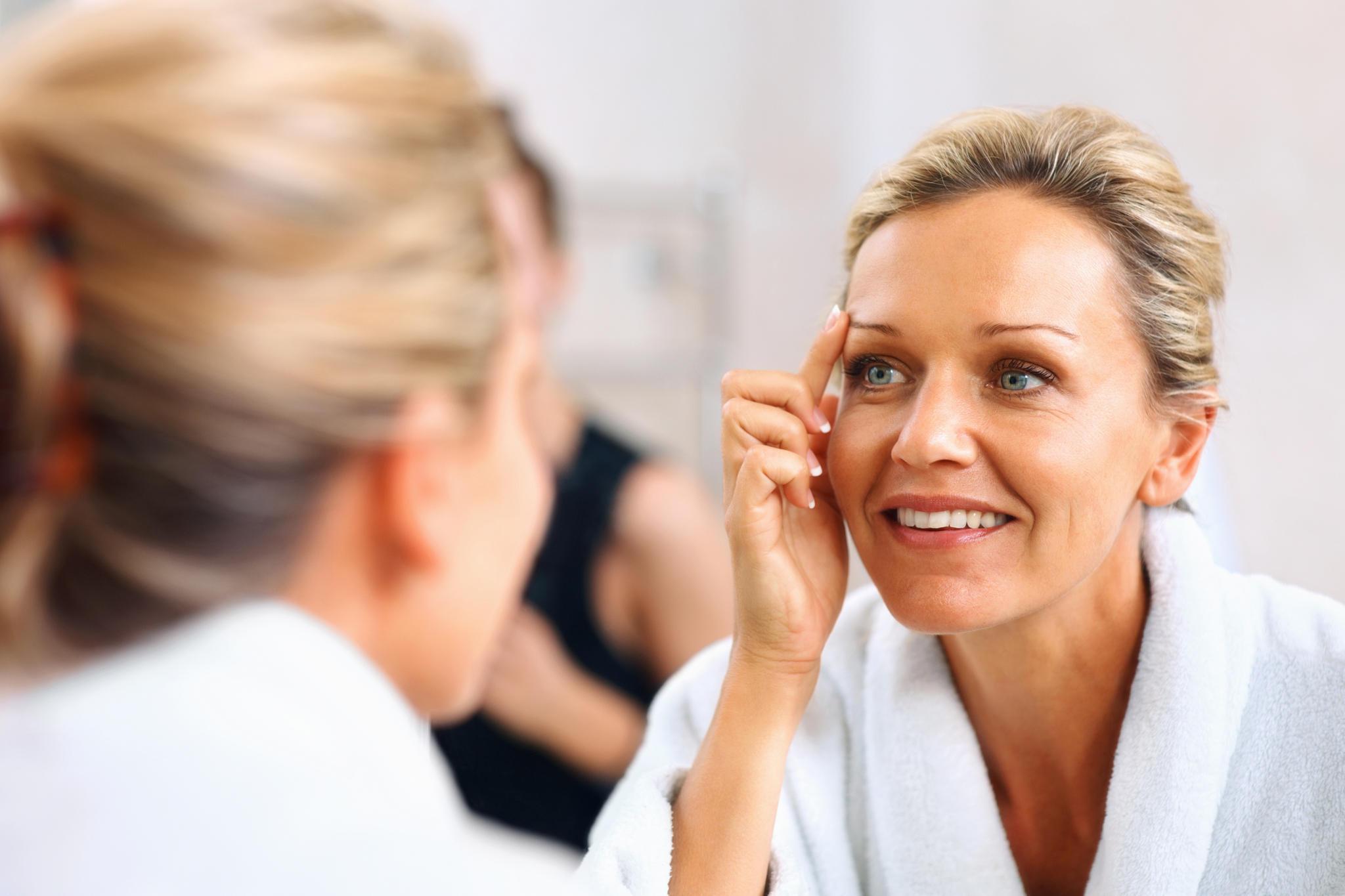 Frau mit strahlender Haut schaut in den Spiegel. Sie trägt einen Bademantel