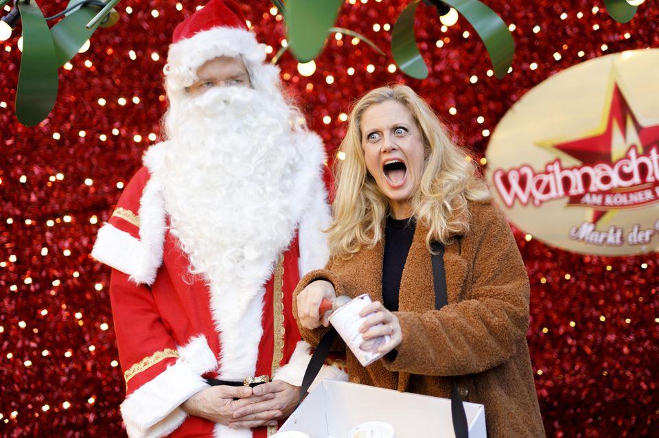 """Wie ein Kind freut sich Barbara Schöneberger gemeinsam mit dem Weihnachtsmann bei der Eis-Bescherung der """"Charlotte Eis-Manufaktur"""" auf dem Weihnachtsmarkt am Kölner Dom eine nicht ganz klassische Nascherei in der kalten Jahreszeit zu verteilen."""