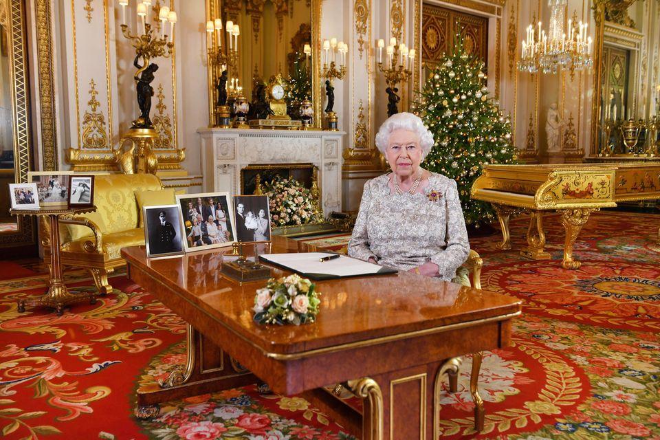 Weihnachten 2018: Queen Elizabeth grüßt aus dem White Drawing Room im Buckingham Palast. Gleich zweimal sind Harry und Meghan auf Fotos zu sehen. Einmal auf einem Gruppenfoto auf dem Schreibtisch und einmal auf einem Foto auf dem Beistelltisch im Hintergrund.