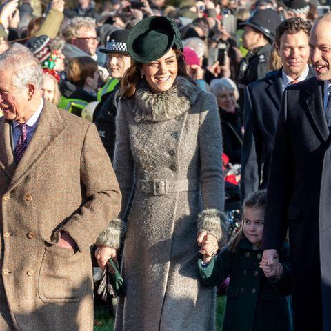 Für den Weihnachtsgottesdienstin Sandringham hat sich Herzogin Kate einen eleganten und kuscheligen Winterlook ausgesucht: Sie trägt einen Mantel von Catherine Walker mit Kunstfell-Elementen. Ein Taillengürtel betont ihre schmale Silhouette. Kates schicke Wildleder-Pumps sowie ihre Clutch stammen von Emmy London und sind perfekt auf die Farbe ihres Fascinators abgestimmt ...