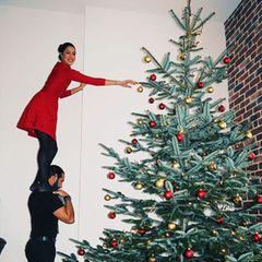 Schwindelfrei geht es für Rebecca Mirhoch hinauf zum Schmücken ihres riesigen Weihnachtsbaums. Auch aufden Schultern ihres Liebstenmacht das Model eine gute (Weihnachts-)Figur.
