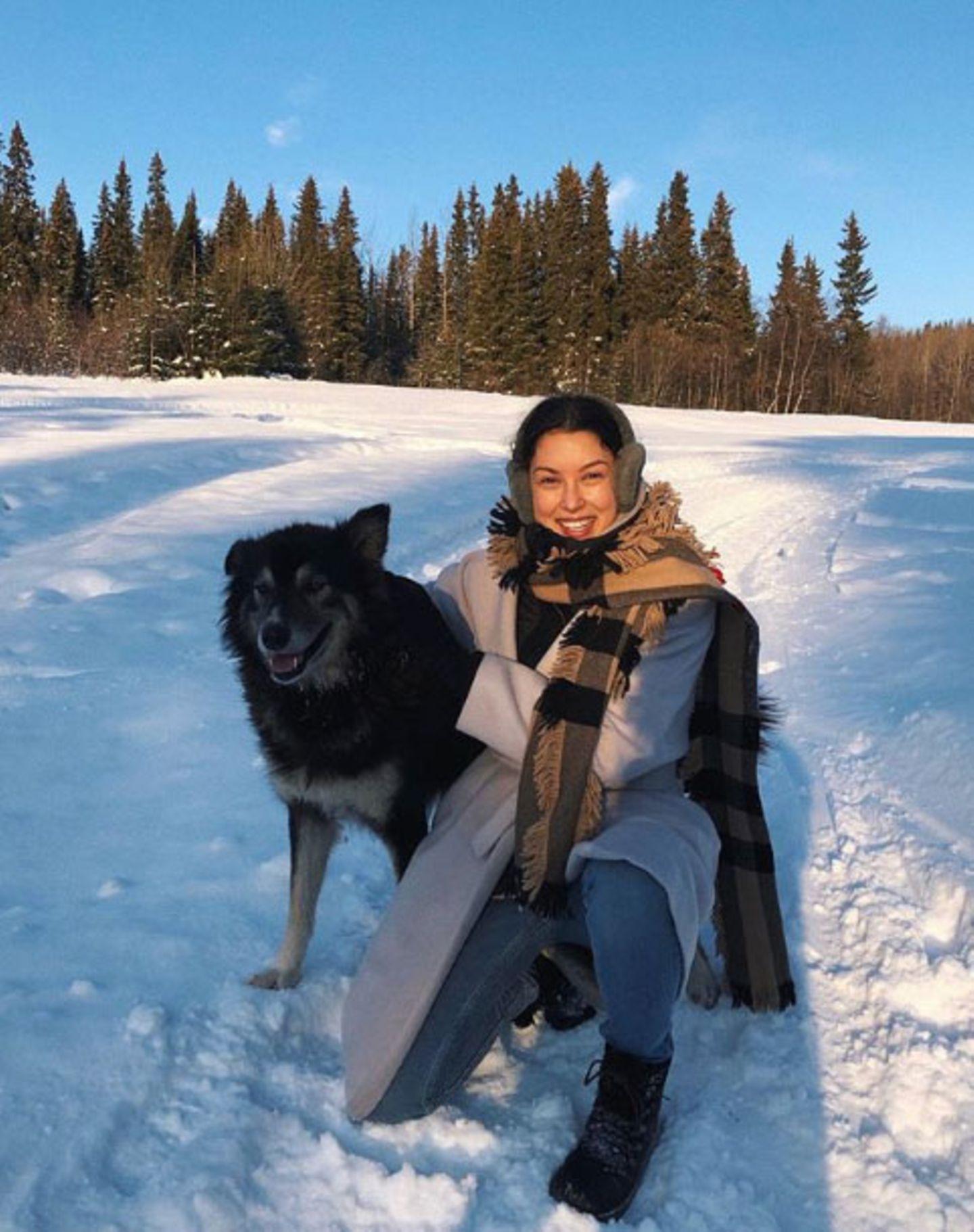 """Dick eingepackt und mit ihrem """"Snow Buddy"""" an der Seitespaziert Rebecca Mir durch die winterliche Landschaft."""
