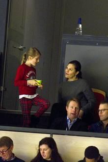 Zu ihrem Dino-Pulli kombiniert Prinzessin Estelle eine rote karierte Hose und kuschelige schwarze Schneeboots. Damit ist sie perfekt für das Eishockeyspiel gerüstet.