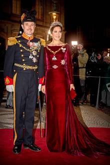 Zum Neujahrsempfang auf Schloss Amalienborg erscheint Prinzessin Mary in einer burgunderroten Robe mit U-Boot-Ausschnitt an der Seite von Prinz Frederik. Während der Schnitt des Kleides, der an den von Herzogin Meghans Brautkleid erinnert, sehr schlicht ist...