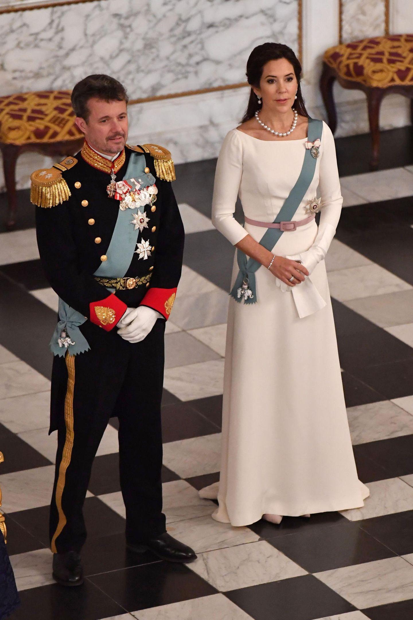 Für einen Empfang auf dem Schloss in Kopenhagen wählt Prinzessin Mary von Dänemark ein erstaunlich ähnliches Kleid. Ihre weiße Robe besticht durch den gleichen klassischen Schnitt, den U-Boot-Ausschnitt, die langen Ärmel und den ausgestellten Rock, das Haar trägt die hübsche Australierin offen. Die Prinzessin peppt das minimalistische Design mitSchärpe, einemrosa-farbenen Gürtel und einer Perlenkette auf.