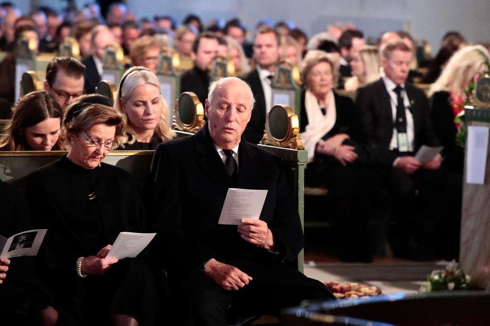 Das norwegische Königspaar Sonja und Harald und dahinter Prinzessin Mette-Marit mit ihrer Tochter Ingrid Alexandra stimmen ein Lied für Ari Behns letzten Weg ein.