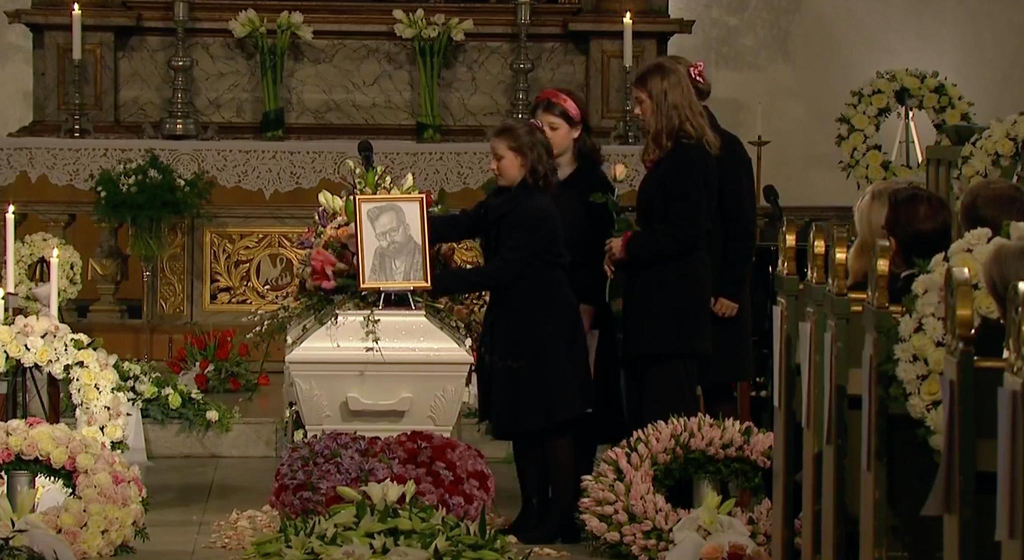 Ari Behns Kinder schmücken seinen Sarg mit weiteren Blumen. Zuvor stellte Maud Angelica ihre Zeichnung auf.