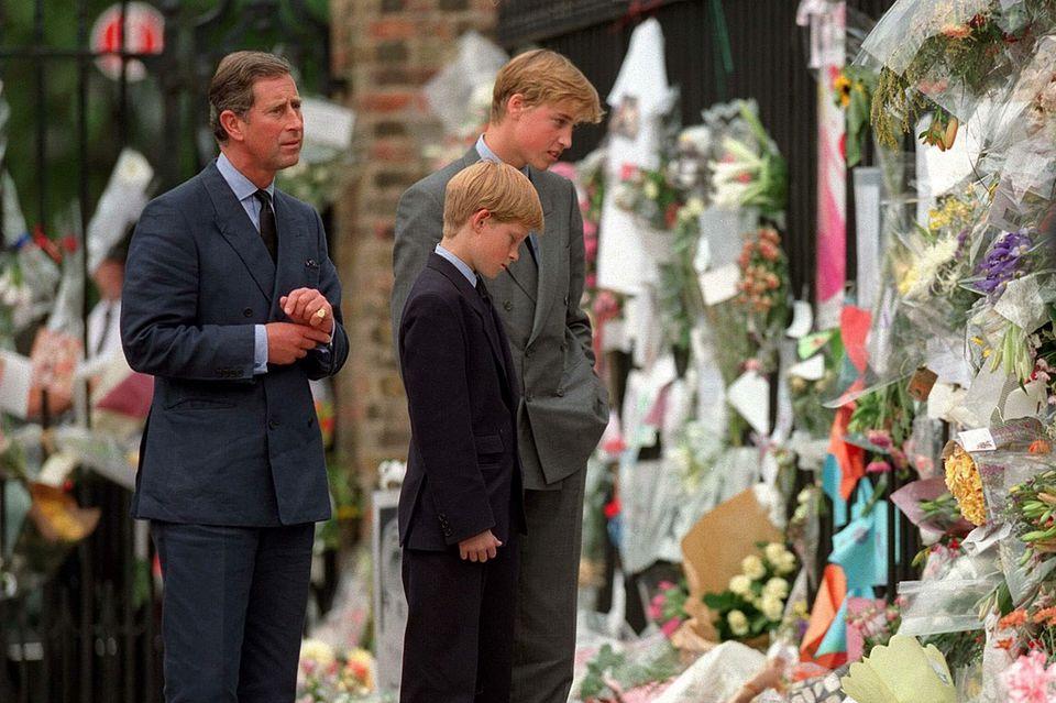 Prinz Charles, Prinz Harry undPrinz William betrachten für Diana abgelegte Trauerblumen und -kerzen.