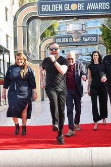 3. Januar 2020  Die Spannung in Hollywood steigt, und der rote Teppich für die 77. Verleihung der Golden Globes ist ausgerollt! Moderator Ricky Gervais freut sich schon sichtlich, ebenso die Organisatoren und links und rechts Dylan und Paris Brosnan. Die Söhne von Pierce Brosnan sind in diesem Jahr dieMessrs. Golden Globe.