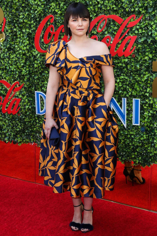 Die 41-jährige Ginnifer Goodwin erscheint mit Vollpony und extravaganterOne-Shoulder-Robe in Orange-Blau auf dem Red-Carpet in Beverly Hills. Das Midi-Kleid des Labels Khoon Hooi mit Satin-Glockenrock verfügt sogar über Taschen, in denen die amerikanische Schauspielerin lässig ihre Hände verstecken kann.