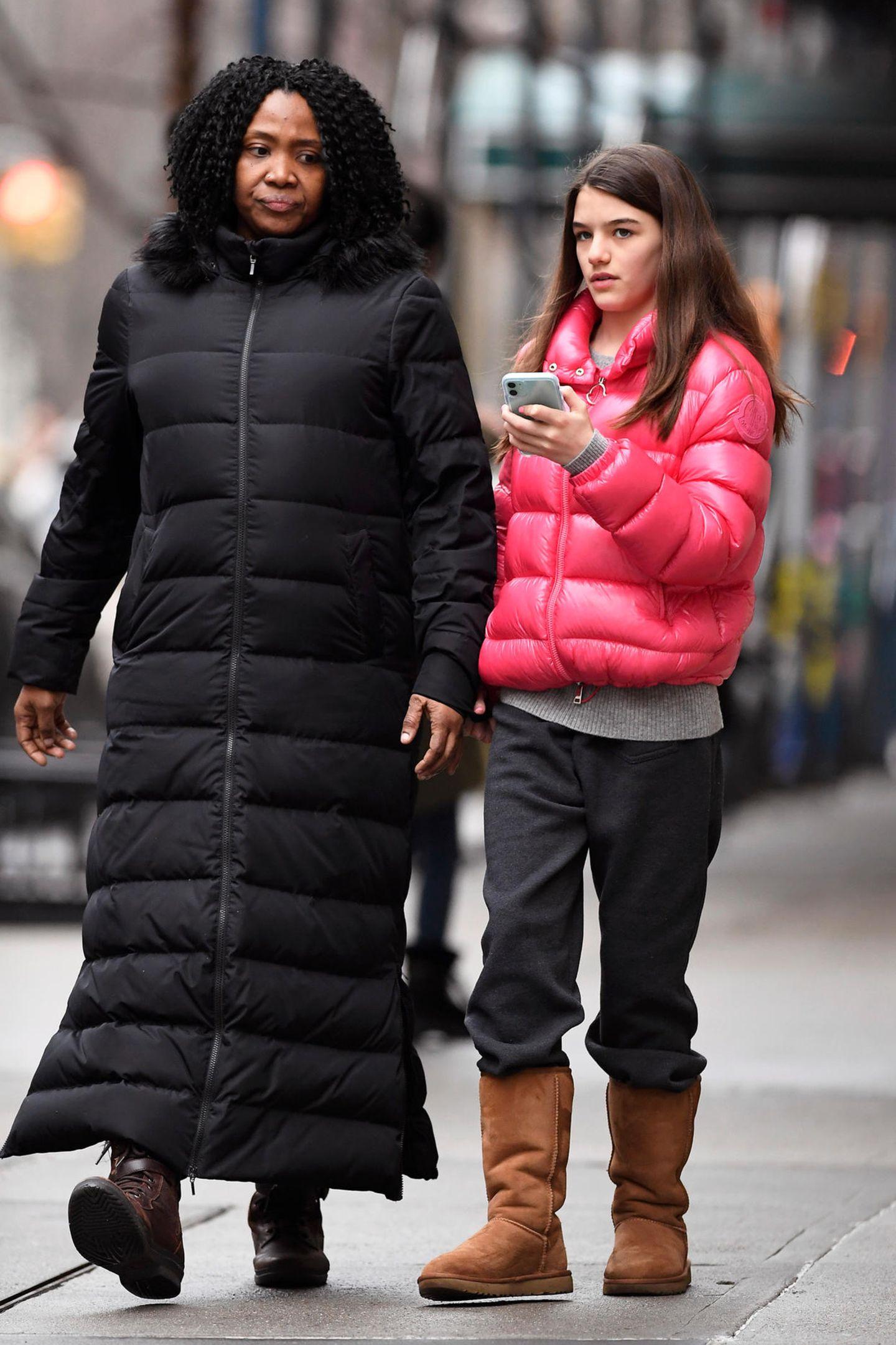 """Der Ausdruck """"Gammellook"""" scheint Suri Cruise durchaus geläufig zu sein. Die Tochter von Katie Holmes und Tom Cruise schlurft mit Jogginghose, Ugg Boots und - dann doch noch ein wenig stylisch - einer knallpinken Daunenjace an der Seite ihrer Nanny durch New York."""