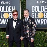 Elton John und Ehemann David Furnish sind mit ikonisch-auffälliger Brille und besticktem Jackett der Hingucker.