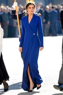 """Die Weihnachtsfeiertage sind nun auch für Königin Letiziavorbei. Am Dreikönigstag wohnt sie der""""Pascua Militärparade"""" in einem atemberaubenden blauen Mantelkleid bei. Es ist Tradition, dass Frauen des Königshofes bodenlange Roben tragen.Letizia weiß genau, wie sie dennoch ihre schönen Beine mit einem langen Schlitz in ihrer Wickelrobe in Szene setzt."""