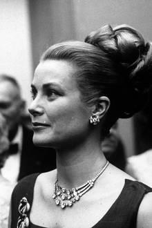 Mit einer ähnlichen, ebenso funkelnden Halskette wird Grace Kelly im Jahr 1960 auf einer Party abgelichtet. Es ist ein großzügiges Präsent ihres Mannes Fürst Rainier III., der ihr das Schmuckstück am Tage ihrer Hochzeit im Jahr 1956 schenkt. Die Diamantenkette wird auf rund 64 Karat geschätzt.