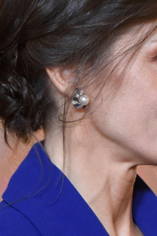 Mit Accessoires hält sich die schöne Monarchin zurück. Das einzige Schmuckstück, welches hinter ihrem tiefsitzenden Chignon-Dutt hervor blitzt, hat jedoch eine rührende Message. Die mit Saphiren und Diamantenverzierten Perlenohrringe warenein Geschenk zur Hochzeit und stammen aus dem Schmuckkästchen vonKönig Felipes Oma, Maria de las Mercedes. Nach fünfzehn Jahren - zum 20. Sterbetag der Gräfin von Barcelona - trägt Letizia die Ohrringe erneut und zollt ihr damit Anerkennung.
