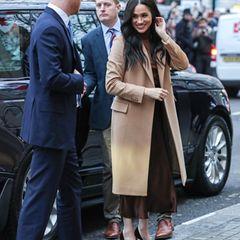 Prinz Harry und Herzogin Meghan sind zurück. In einem beigen Mantel und einer tollen Kombi aus braunem Satinrock von Massimo Dutti und braunem Rollkragenpullover zeigt sich eine strahlende Meghan bei ihrer Ankunft am Canada House in London.