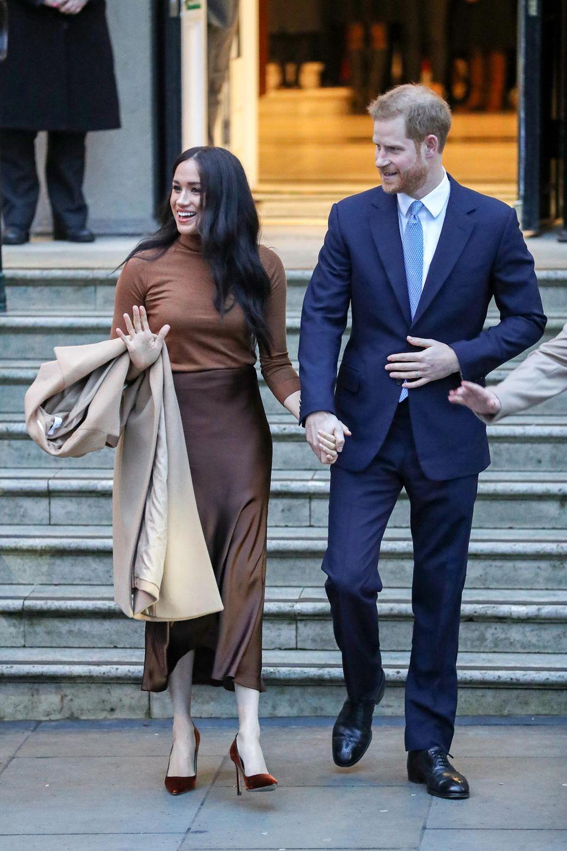 """Das royale Paar verlässt mit 15-minütiger Verspätung das """"Canada House"""" am Londoner Trafalgar Square. Weil Meghan ihren Mantel für den kurzen Weg zum Auto nicht wieder anzieht, kommt ihre braun-in-braun-Kombi noch besser zur Geltung."""