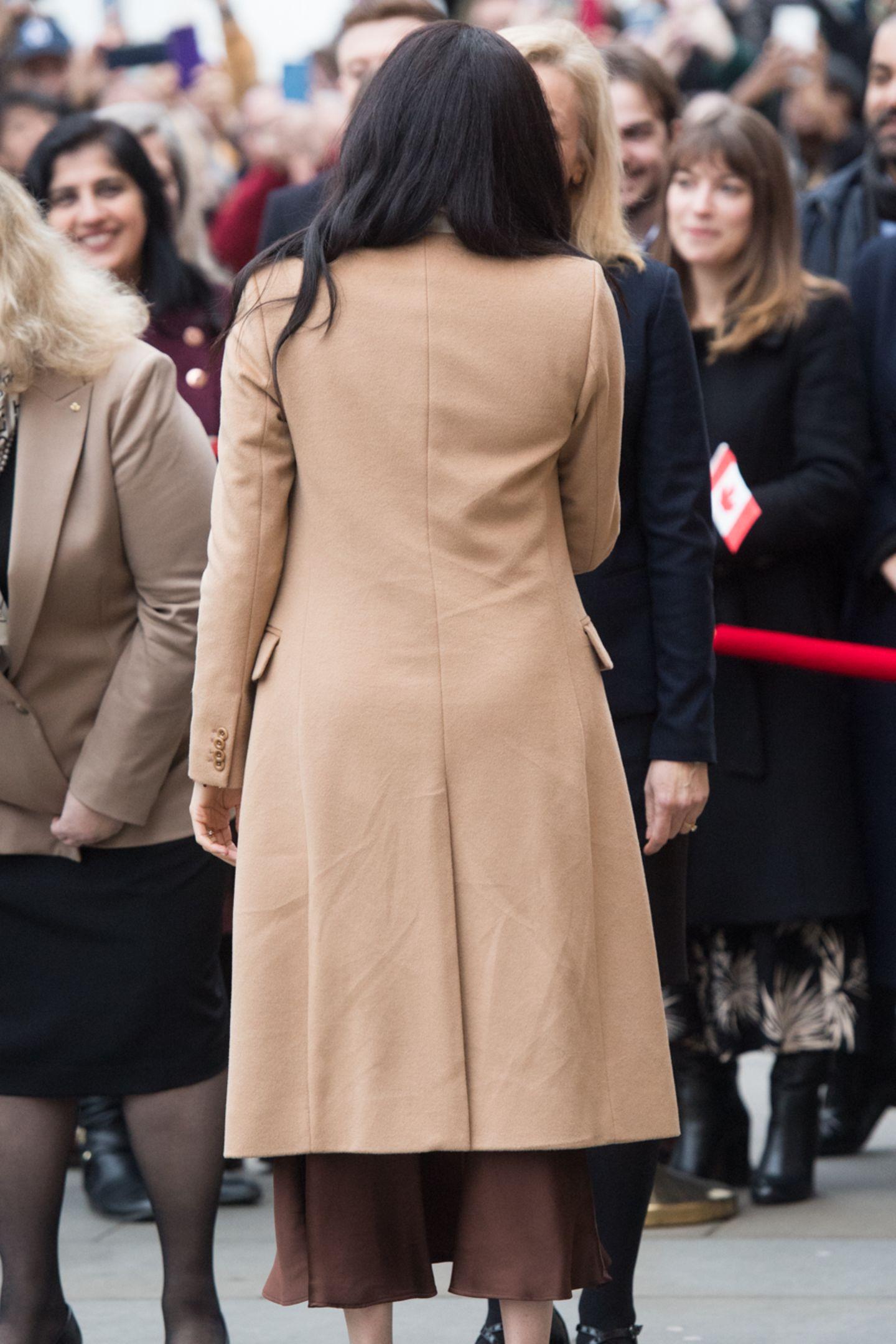 Die Herzogin entscheidetsich bei diesemAuftritt für eine Braun-in-braun-Kombi. Der Mantel von Reiss passt ausgezeichnet zu dem Look, jedoch wurde der Faden, der den Schlitz des Mantel provisorisch zusammenhält, nicht fachgerecht entfernt. Von hinten mag das nicht sofort ins Auge zu fallen...