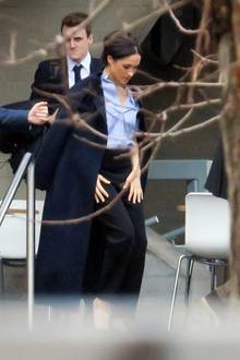 """Back to Business: Gehüllt in einen marineblauen Wollmantel von Massimo Dutti wird Herzogin Meghan in London gesichtet. Für den Besuch des National Theaters wählt sie einen schicken Business-Look, der an ihre vergangene """"Suits""""-Zeiterinnert. Zu einem blauen, weit aufgeknöpften Hemd, das sie in ihre schwarze Anzughose gesteckt hat, trägt die Herzogin elegante Pumps. Außerdem hat sie ihre langen Haare ganz ladylike zu einer Hochsteckfrisur zusammengebunden."""