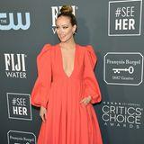 Olivia Wilde beweist Mut zur Farbe und wählt für den Red Carpet ein tief ausgeschnittenes Kleid von Valentino in Orange.