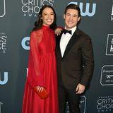 Frisch verlobt und strahlend schön:Chloe Bridges und Adam DeVine posieren Arm in Arm für die Fotografen. Während sie auf ein knallrotes Dress von Azeeza setzt, erscheint er im klassischen Anzug mit Samtrevers.