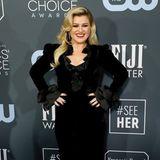 Kelly Clarkson setzt auf ein ausgefallenes Design von Alessandra Rich. Volants an Revers und Ärmelsaum machen das schwarze Samtkleid mit Beinschlitz noch besonderer, die Shoulderpads unterstreichen ihre Silhouette.