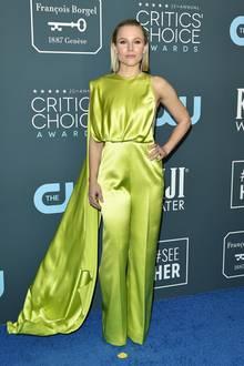 Kristen Bell ersetzt das klassische Abendkleid durch einen Satin-Jumpsuit in einem giftigen Grün. Zusätzlicher Hingucker ist der drapierte Schleier.