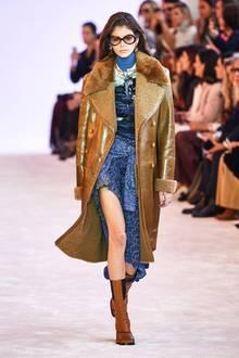 Bereits im Februar 2019 präsentiert Kaia Gerber den braunen Designermantel auf dem Catwalk der Fashion Week in Paris. Der Look des Models ist für diesen Anlass betont dramatisch: So trägt Kaia eine XL-Sonnenbrille und Lederstiefel, als sie über den Laufsteg stolziert und sorgt mit dem schönen Braun-Blau-Kontrastfür Begeisterung in der Front Row.
