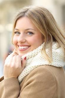 Frau im Winter lächelt in die Kamera und wärmt sich die Hände.