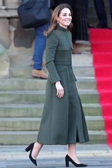 """Business as usual! Eine strahlende Herzogin Catherine zeigt sich beim ersten offiziellen Termin seit der Megxit-Krise. Auch ihr Outfit schreit: """"Unser Leben geht ganz normal weiter!"""" Sie trägt einen langen dunkelgrünen Mantel von Alexander McQueen - einem ihrer absoluten Lieblingslabels. Auffällig ist nur, dass sich die sonst so protokoll-bewusste Frau von Prinz William an diesem Tag gegen eine Strumpfhose entscheidet."""