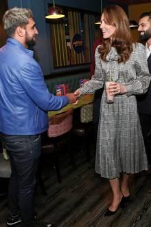 Unter dem Designermantel trägt Catherine ein grau-kariertes Kleid von Zara. Der schienbeinlange, plissierte Rock, die leicht gepufften Ärmel und die Schleife unterstreichen ihreFeminität und die schlankeFigur der Dreifachmama. Dazu ist es ein echtes Schnäppchen, kostet reduziert nur 18 Euro!