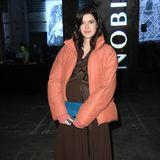 Bei der Runway-Show von Nobi Talai, zeigt sich Marie Nasemann in einem braunen Dress, das dank eines Gürtels in der Taille ebenfalls ihren Babybauch betont. Dazu trägt sie bequeme Sneaker und eine warme Jacke in einem fröhlichen Lachs-Ton.