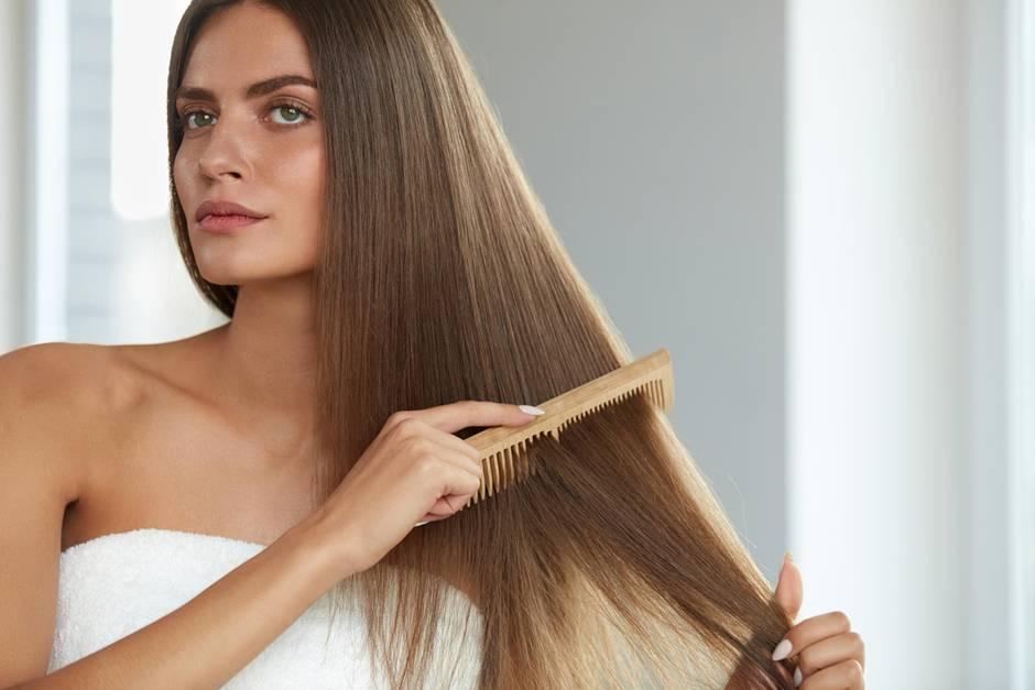 Frau kämmt ihre Haare