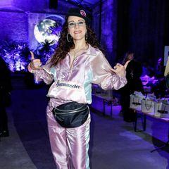 ... trägt Sängerin Blümchen einen bequemen Look in Trainingsanzug-Optik. Der sportliche Zweiteiler schimmert im Rampenlicht und zieht die Blicke der übrigen Fashion-Show-Gäste auf sich. EineschwarzeKäppi und eineXL-Bauchtasche runden Blümchens 90er-Jahre-Gedächtnis-Look ab.