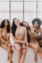 Fünf Frauen tragen Shapewear auf Fensterbank und lachen