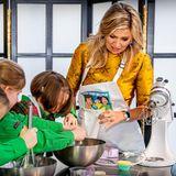 """Königin Maxima besucht die """"Scouting Netherlands"""" anlässlich des 100-jährigen Bestehens der Organisation.Mit Kindern zwischen 7 und 11 Jahren greift sie zu Schneebesen, Rührmaschine und Mehl um Cup Cakes zu backen. Ganz reibungslos funktioniert das aber nicht, schaut man sich den skeptischen Blick von Máxima an. Ups!"""